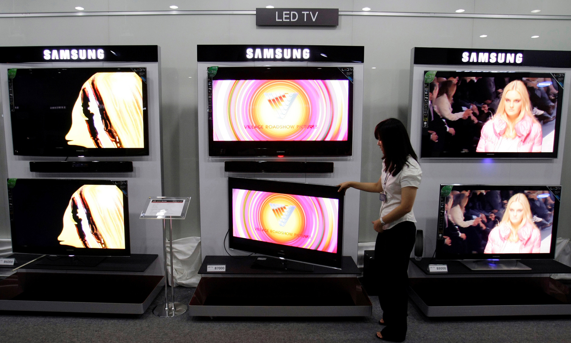 An employee of Samsung Electronics Co. is seen adjusting a LED TV at the company's showroom in Suwon, south of Seoul, South Korea in this July 14, 200...
