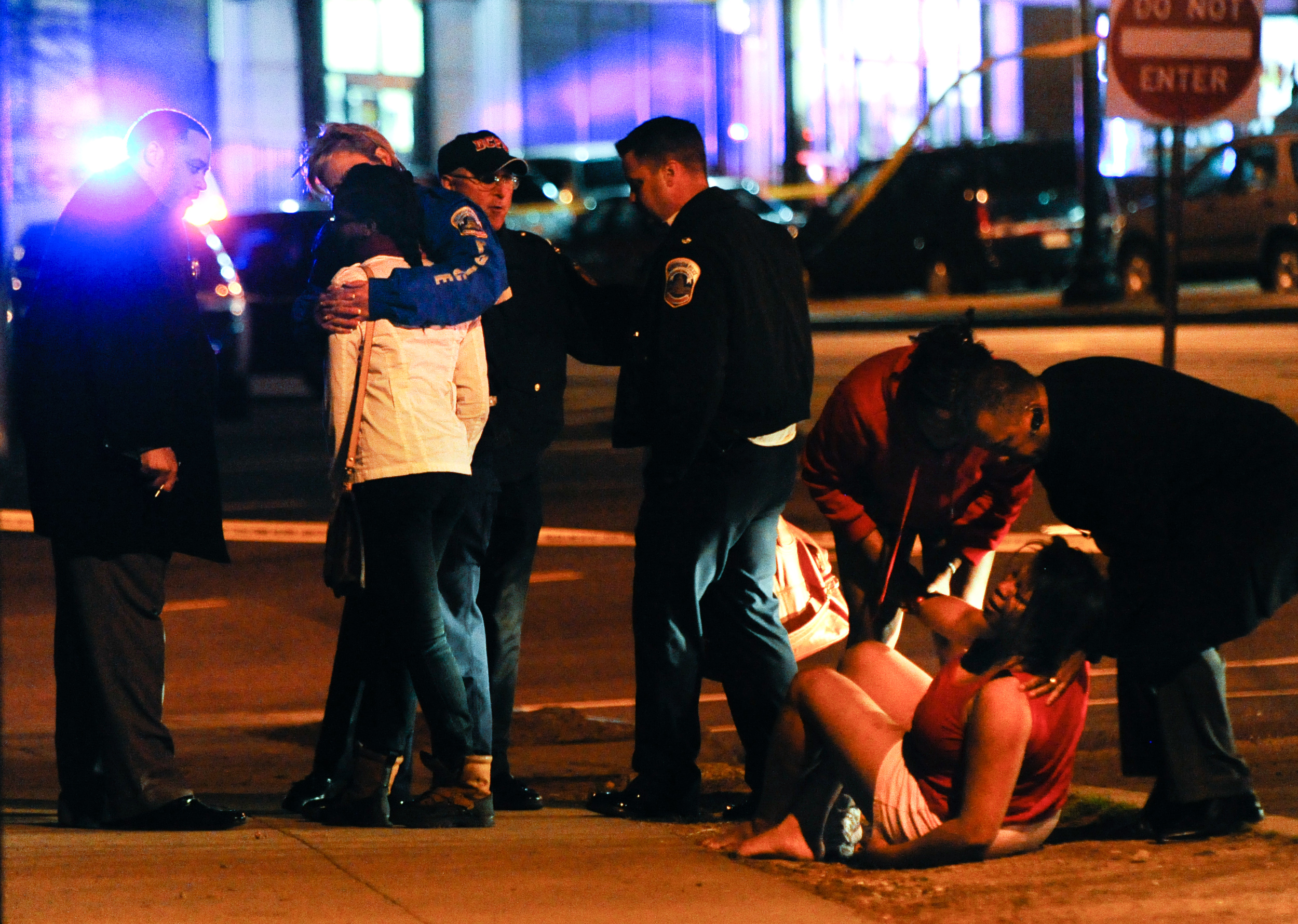 Chief Cathy Lanier, blue jacket, second from left, and other police attend to the scene of a multiple shooting with fatalities on South Capitol Street...