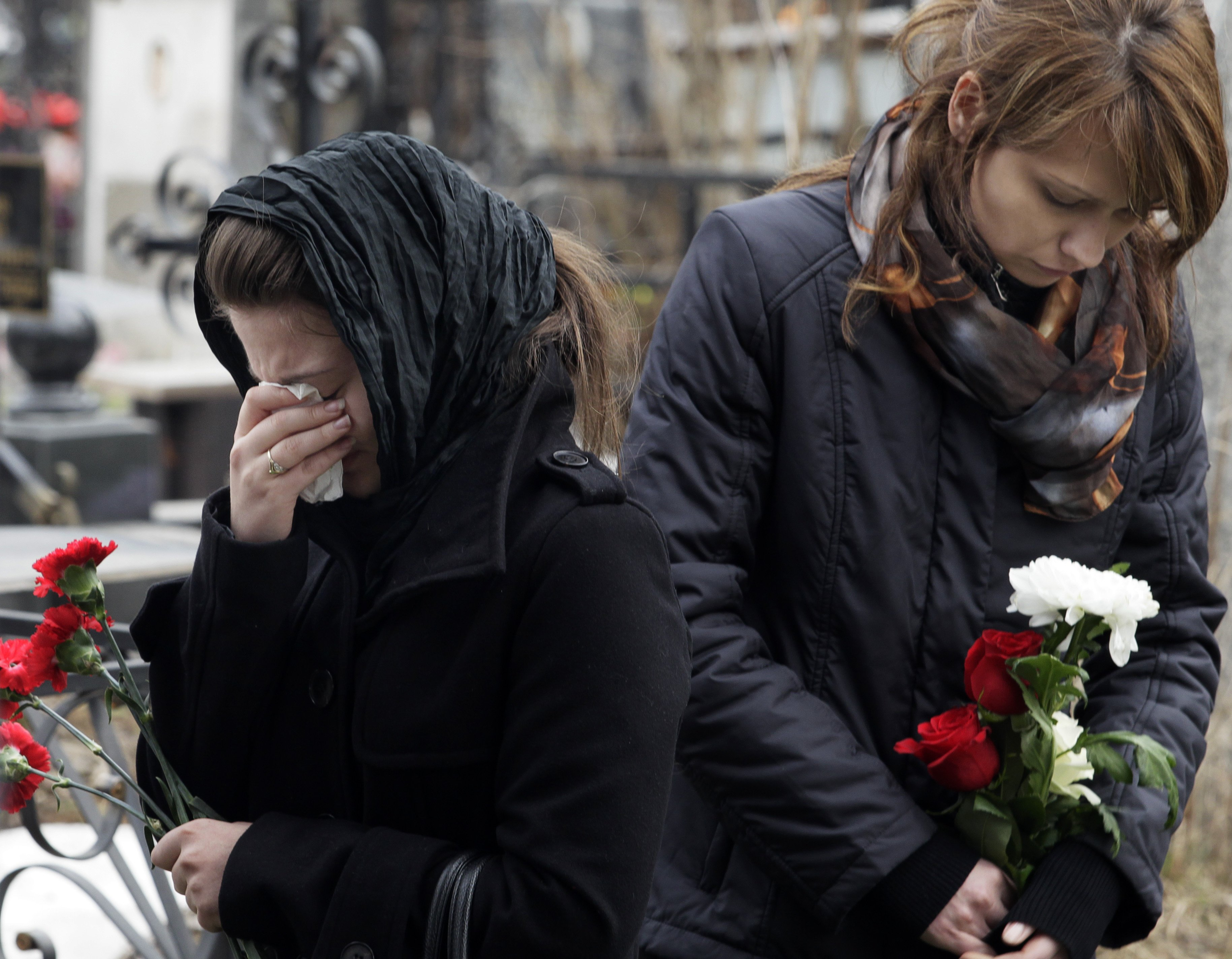 Relatives and friends react next to the coffin of Anna Permyakova, 35, during a funeral ceremony for victims of subway blasts in Moscow, at a cemetery...