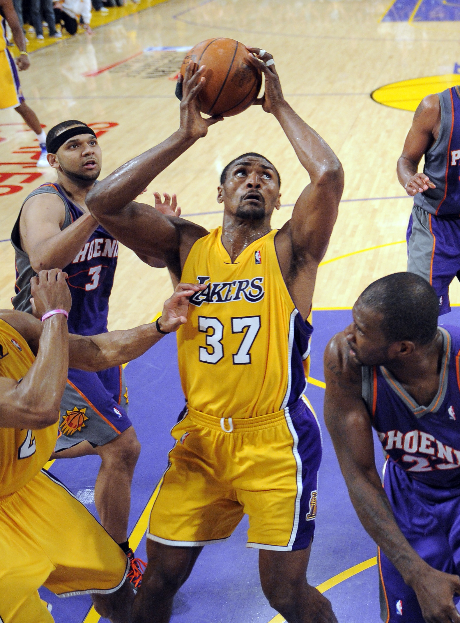 Los Angeles Lakers forward Ron Artest puts up the winning shot as Phoenix Suns forward Jared Dudley, left, and guard Jason Richardson look on during t...