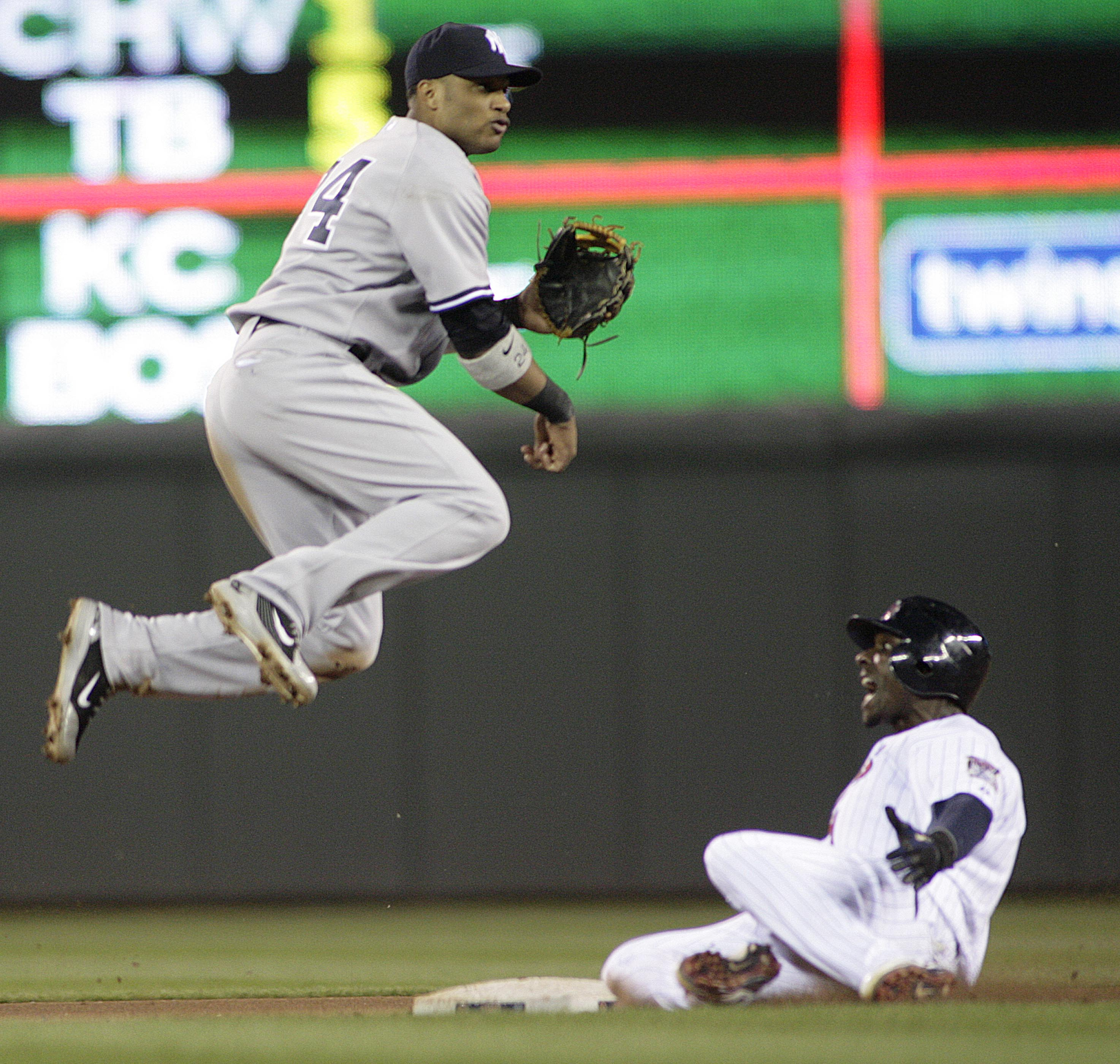 New York Yankees second baseman Robinson Cano, left, watches his throw to first after he forced out Minnesota Twins?Orlando Hudson on the first half o...