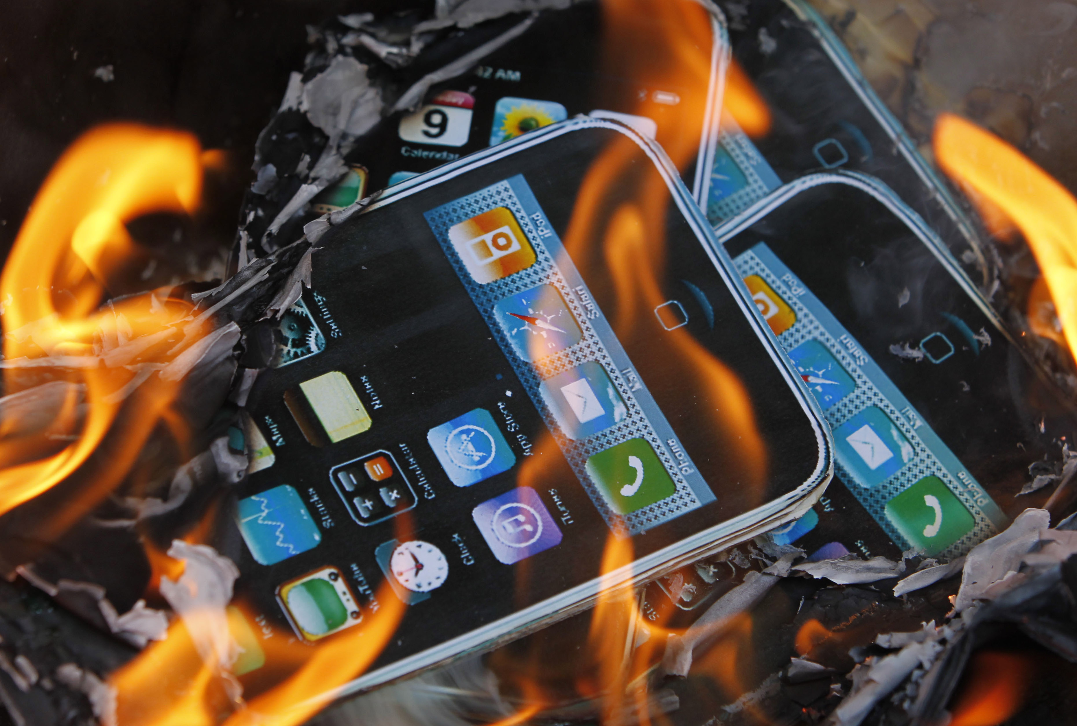 Cardboard cutouts resembling iPhones are sent on fire by labor activists near the Foxconn office in Hong Kong on May 25.