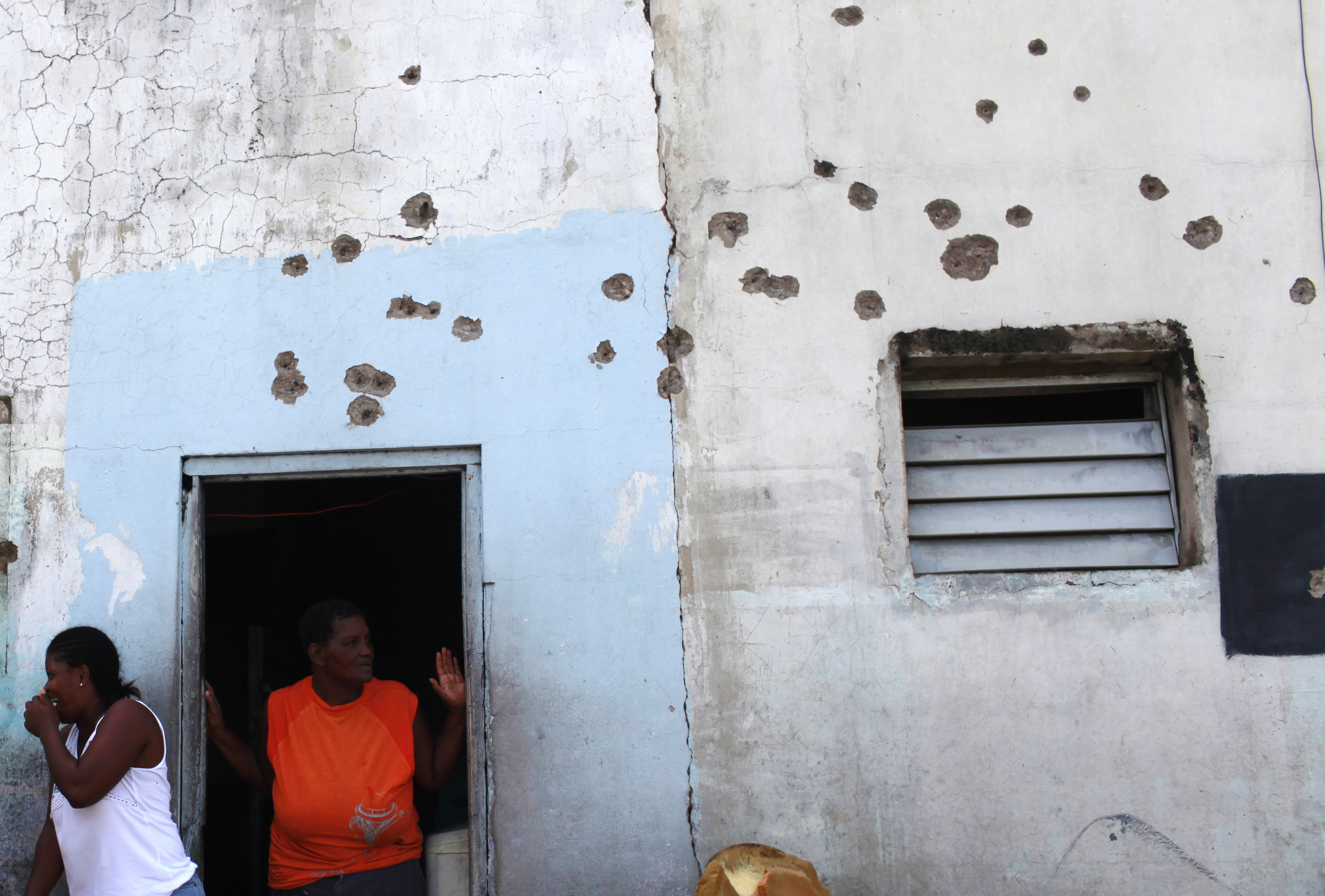 Residents gather outside their bullet-riddled home during a media tour organized by government authorities inside the Tivoli Gardens neighborhood in K...