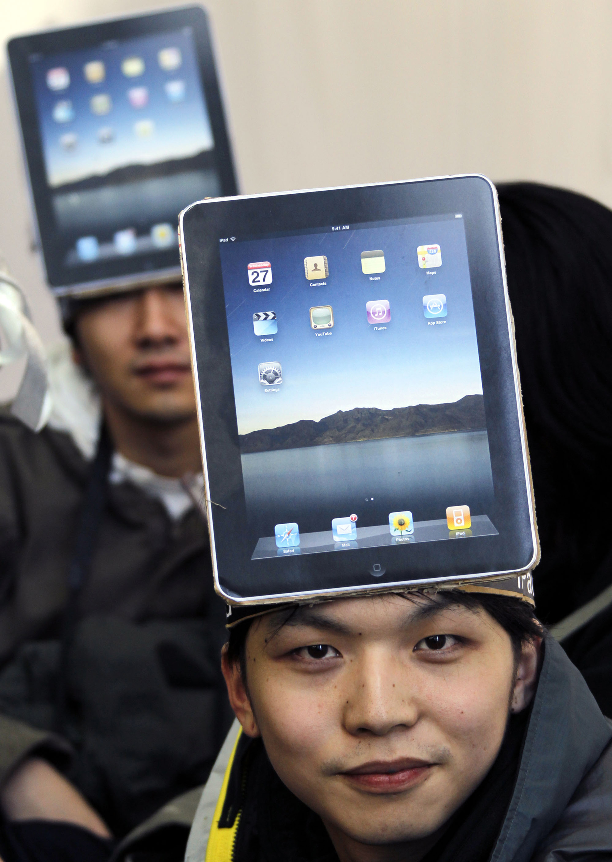 Mitsuru Endo, a Japanese fan, wears a cutout of Apple's iPad on his head as he waits his turn to buy Apple's new tablet device at a Softbank Corp. sto...