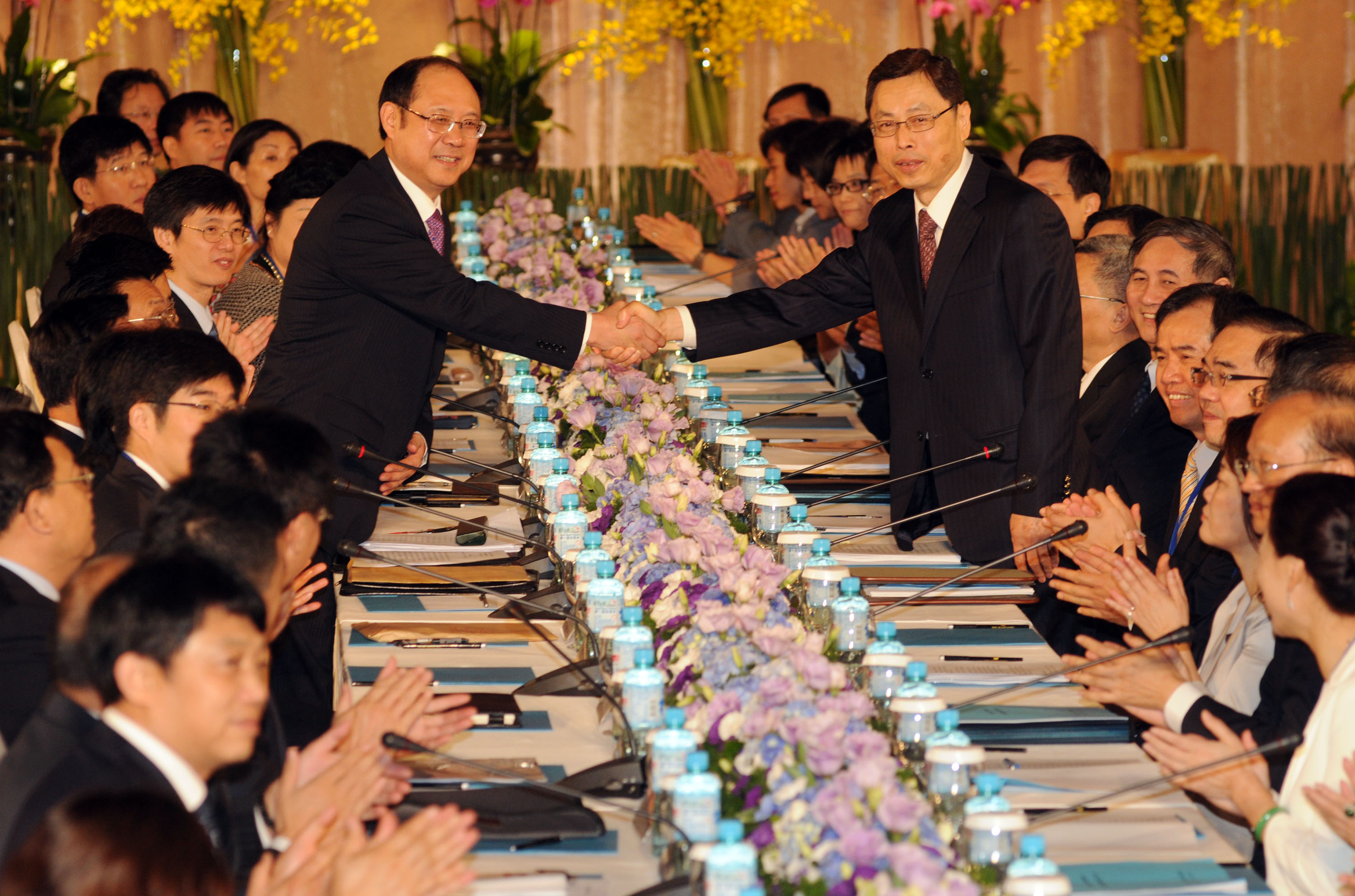 Taiwan's Straits Exchange Foundation Vice Chairman Kao Koong-lian, right, shakes hands with China's Association for Relations Across the Taiwan Strait...