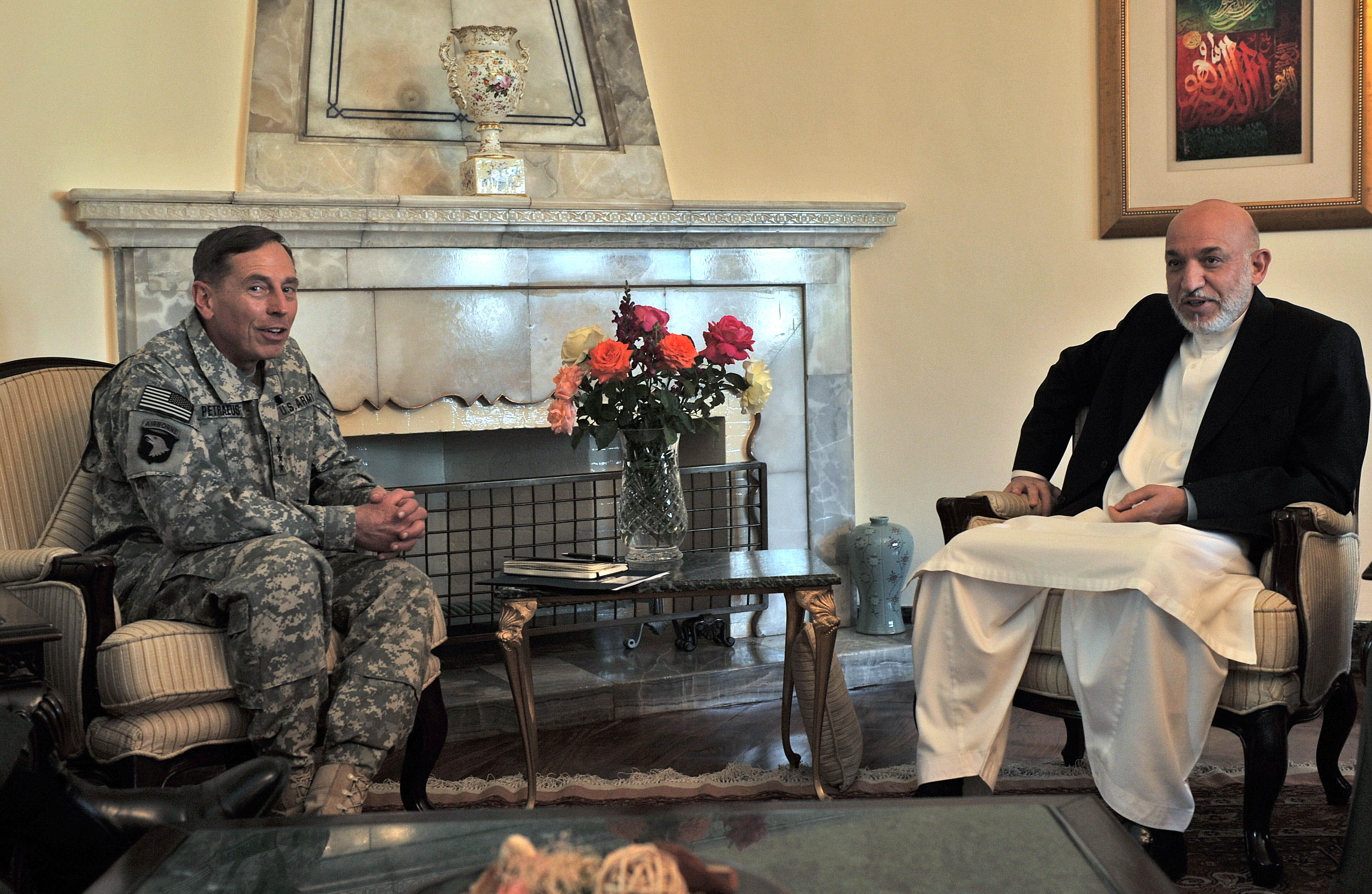 Afghan President Hamid Karzai, right, and commander of NATO forces in Afghanistan U.S. Gen. David Petraeus talk during a meeting at the Presidential P...