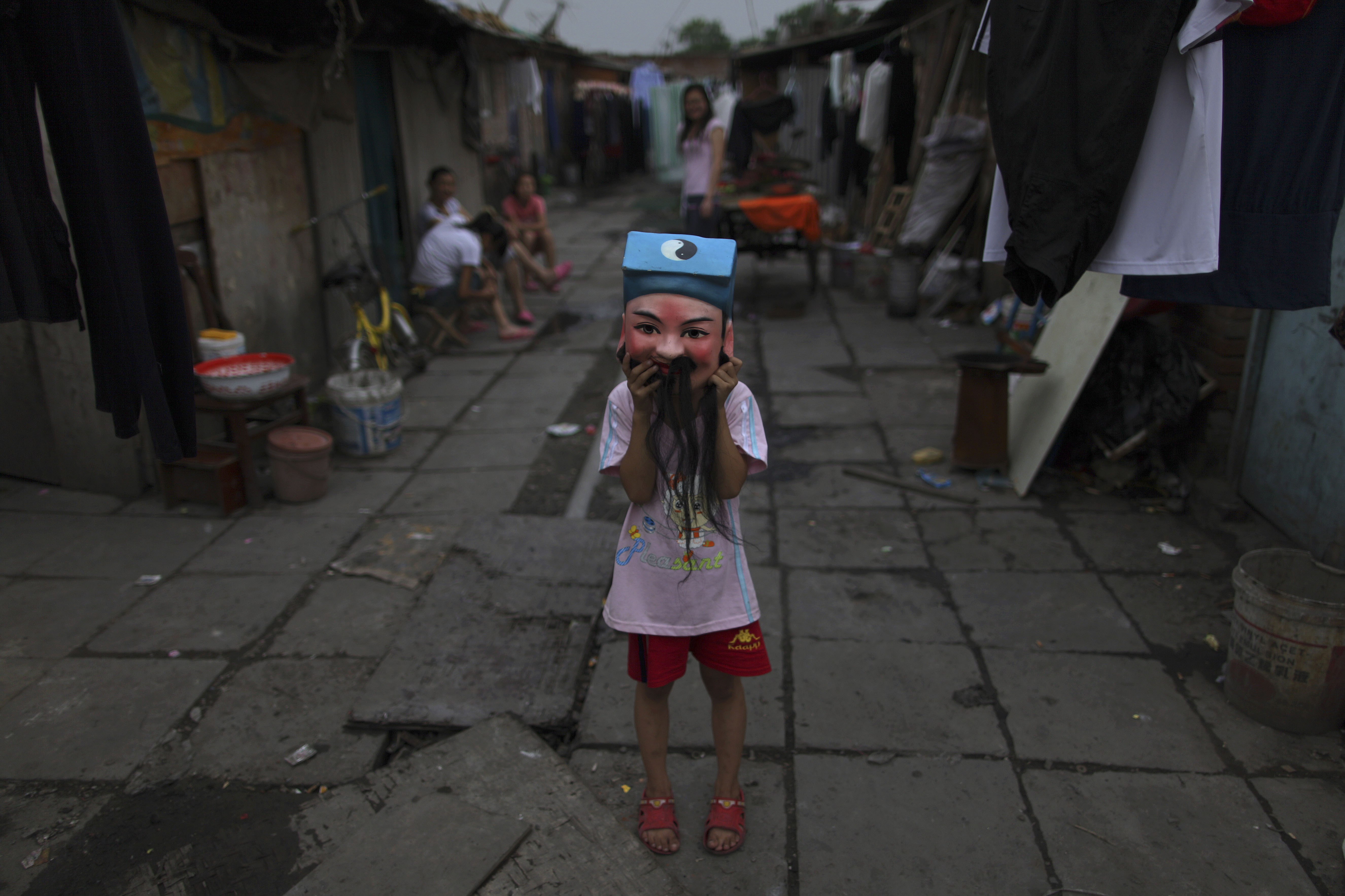 A Chinese girl puts on a mask while playing with other children in a hutong, or a traditional alleyway in Beijing, China on Wednesday.