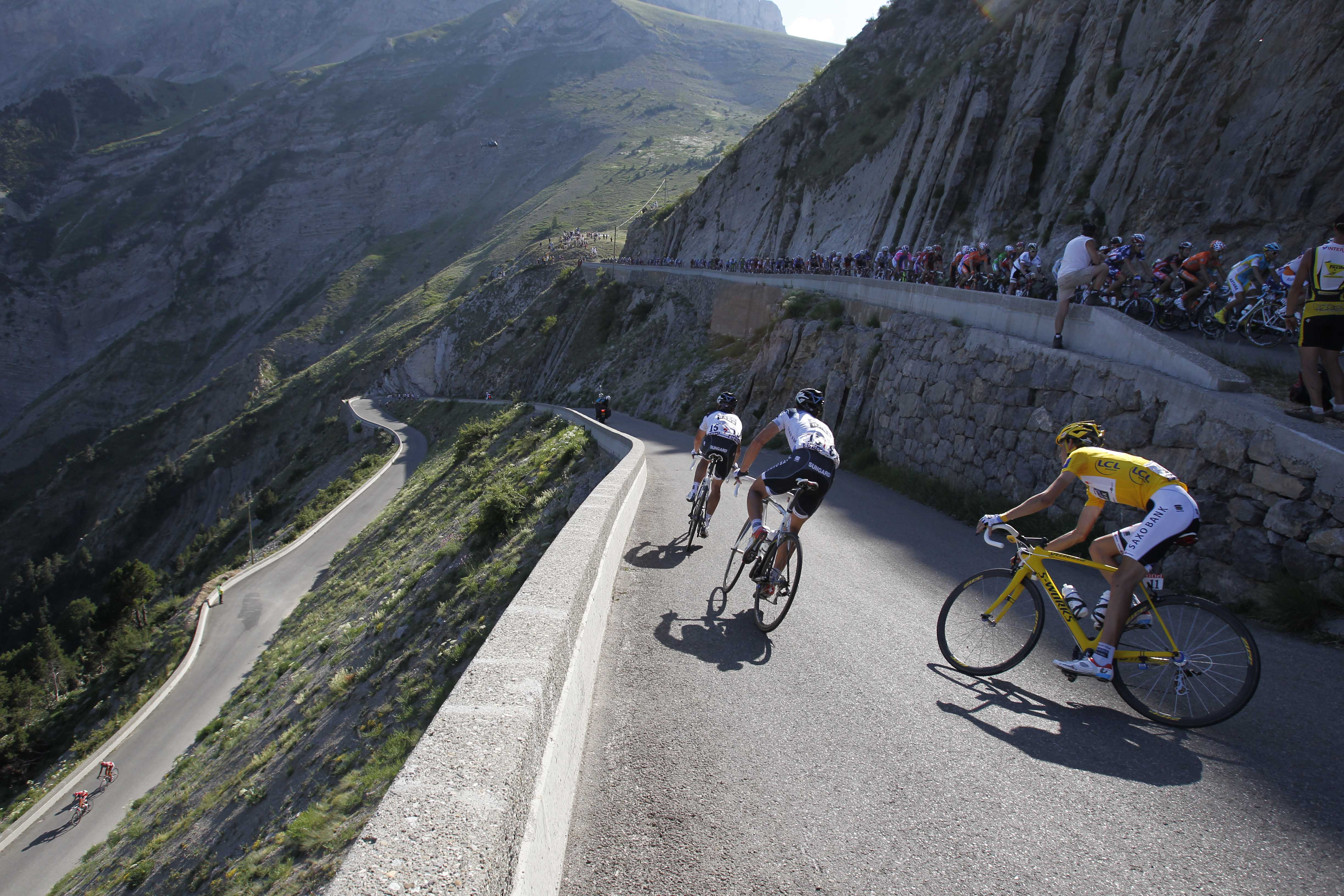 The pack with Andy Schleck of Luxembourg, wearing the overall leader's yellow jersey, foreground right, speeds down Noyer pass during the 10th stage o...