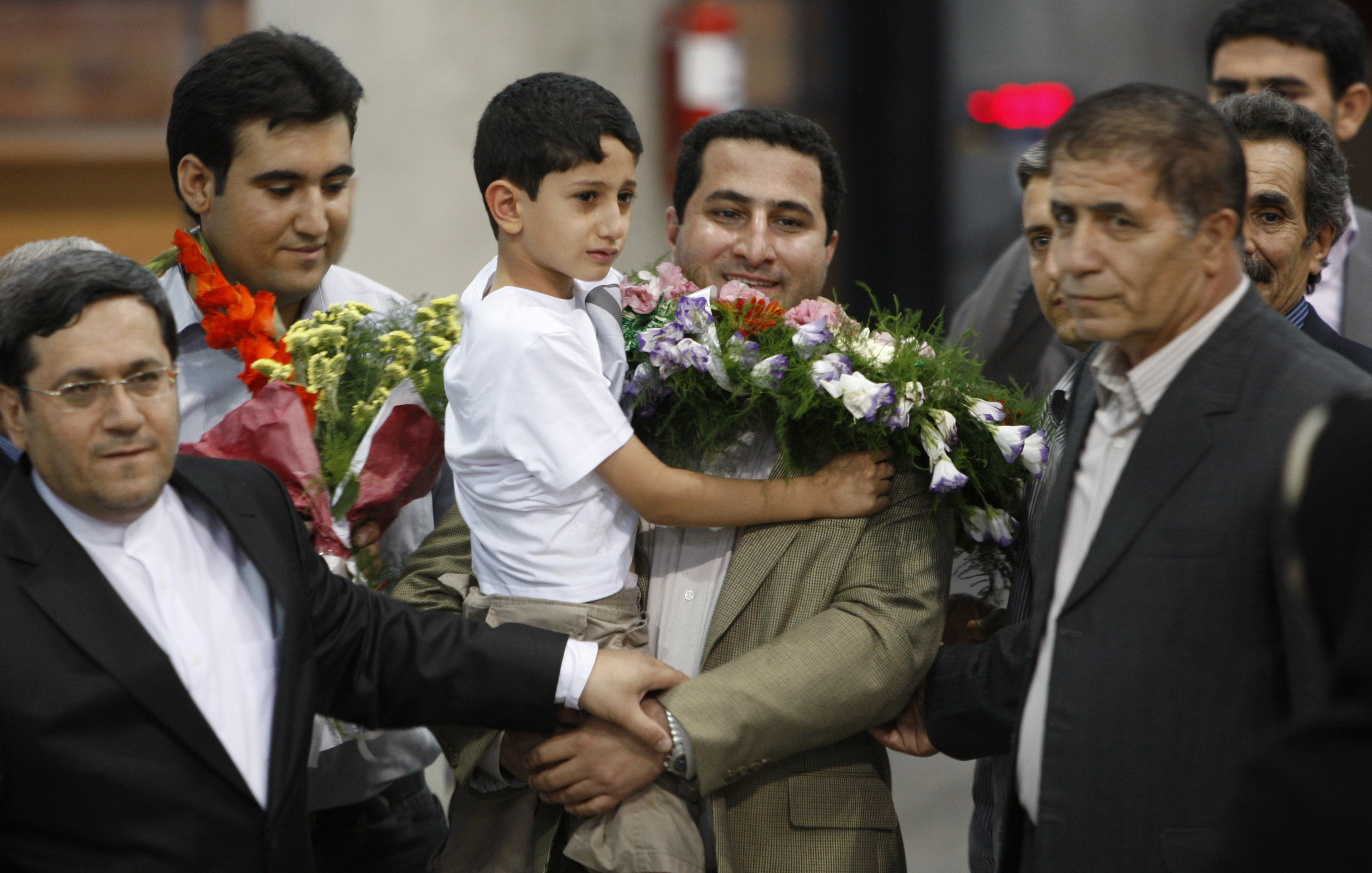 Shahram Amiri, an Iranian nuclear scientist who disappeared a year ago, center, holds his 7-year-old son Amir Hossein as he arrives at the Imam Khomei...