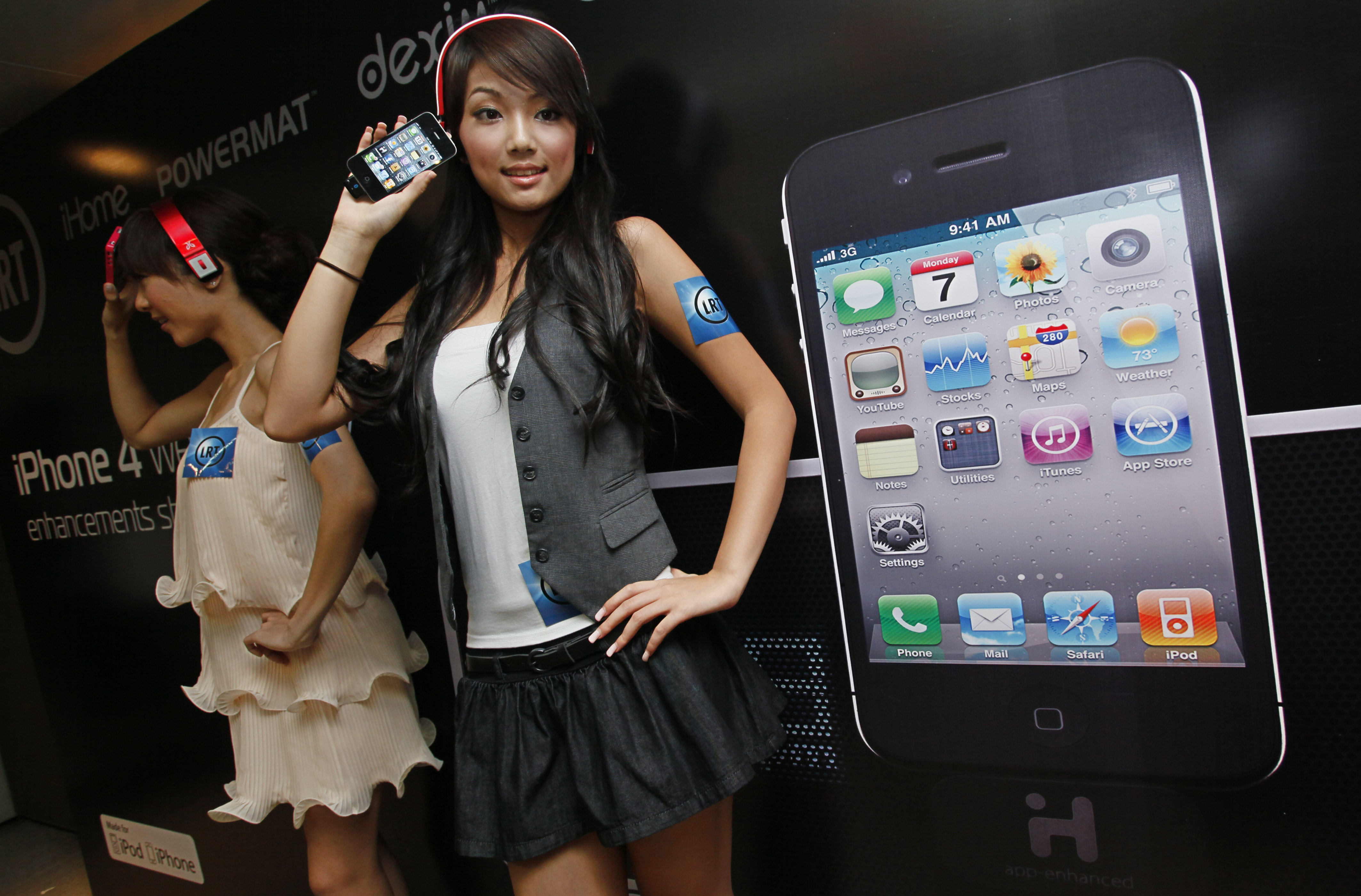 Models hold the iPhone 4 during a promotional event in Hong Kong on Thursday.