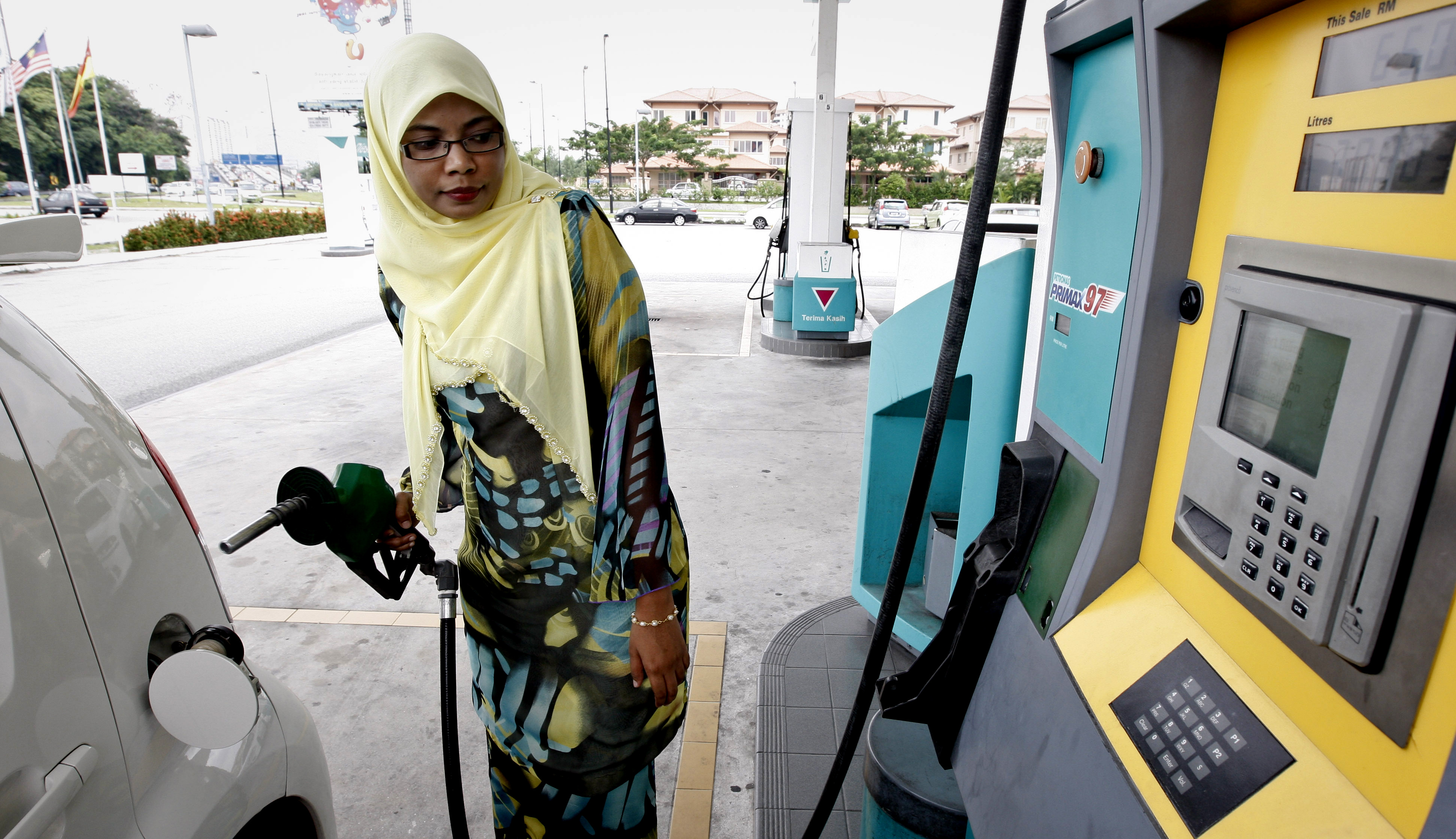 A female driver fills up petrol at a gas station in Kuala Lumpur, Malaysia on Friday. Malaysia cut fuel and sugar subsidies on Friday, the first in a ...
