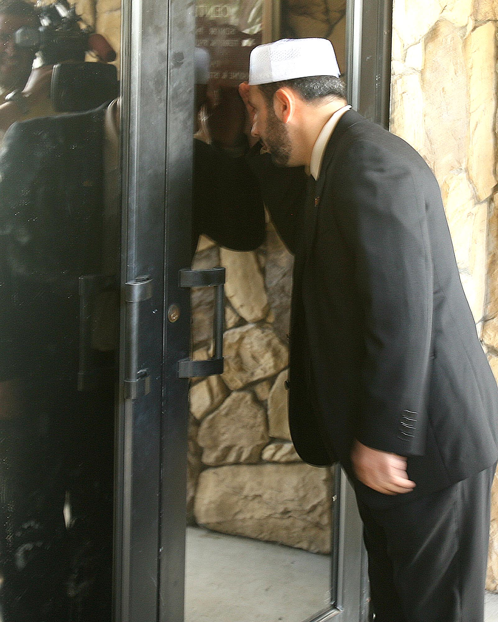Imam Muhammad Musri, of the Islamic Society of Central Florida, peeks into the window at the Dove World Outreach Center in Gainesville, Florida on Wed...