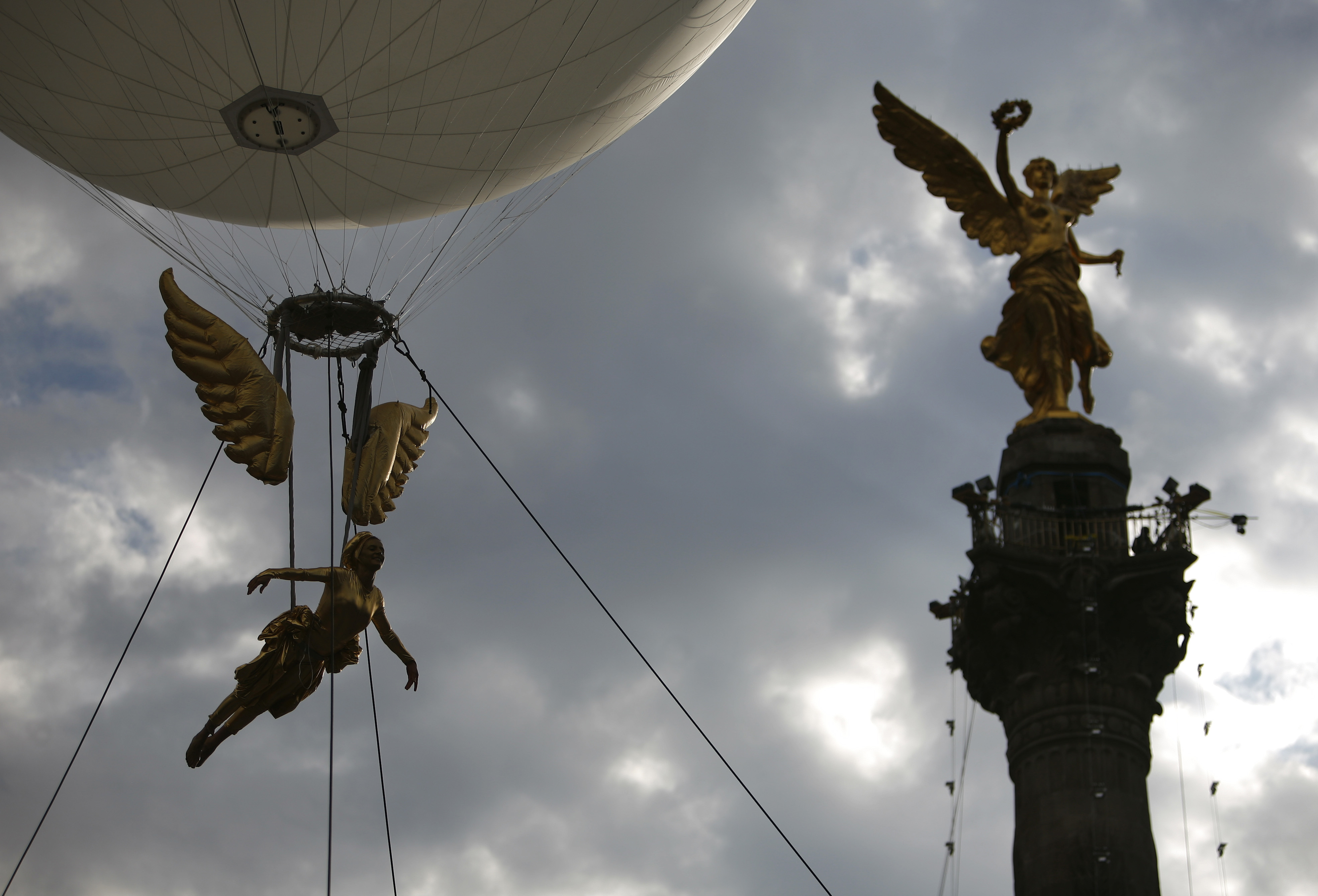 A person dressed in the likeness of the Angel of Independence, left, floats by the Angel of Independence monument during a bicentennial parade in Mexi...