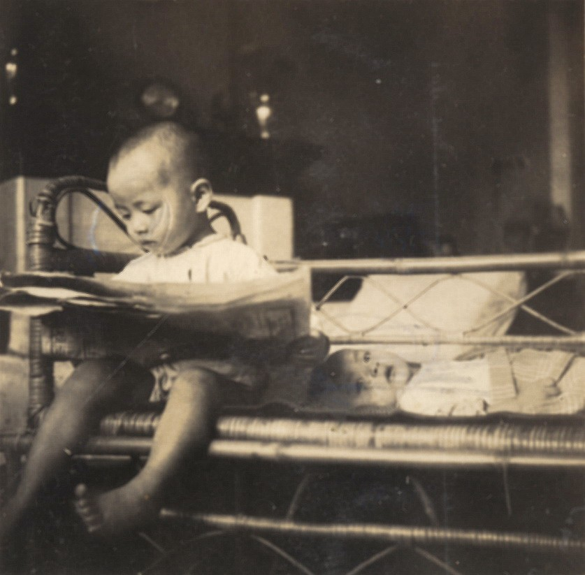 這張照片中姚仁祿當時3歲,看似拿著報紙在讀,其實拿反了,他推測這或許可看出自己從小對看文字有興趣,縱然看不懂。(姚仁祿提供)