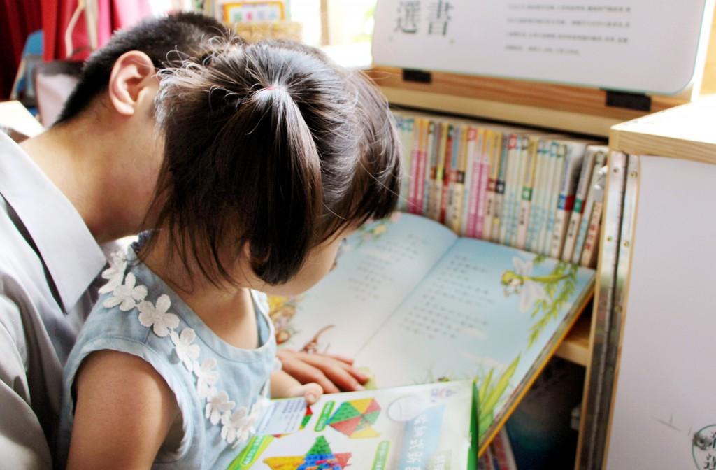 收容人陪孩子一起挑書,一起閱讀;彼此之間享受過去從未有過的心靈交流。(新北市圖萬里分館提供)