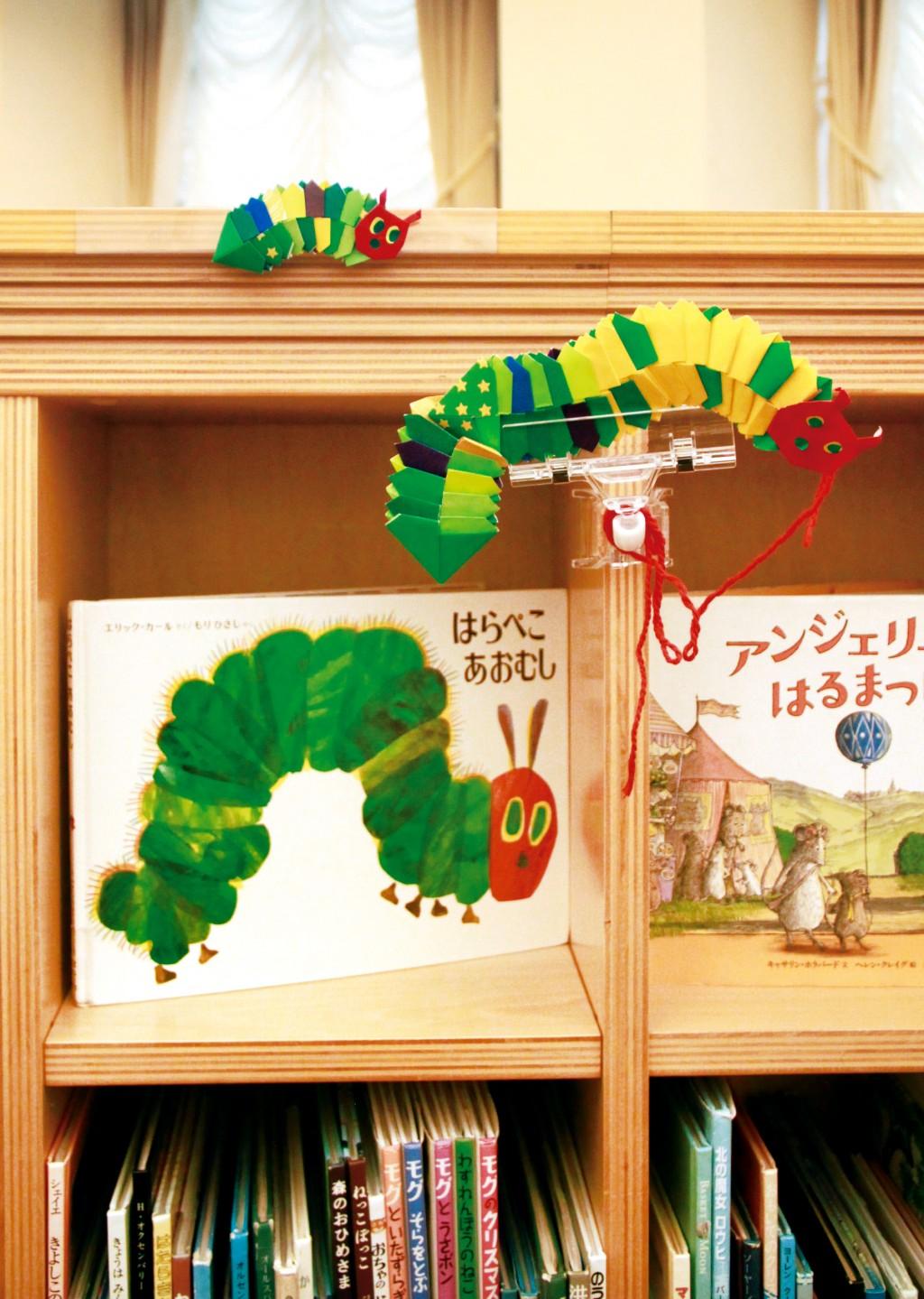 書櫃上陳設出館員製作《好餓的毛毛蟲》繪本角色紙偶。