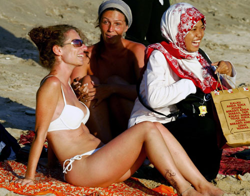 An Indonesian Muslim tourist poses for pictures with tourists sunbathing on Kuta Beach at the Indonesian resort island of Bali over the weekend.