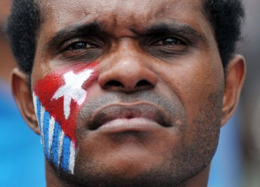 A Papuan protester with his cheek displaying the banned Morning Star flag takes part in a rally to mark the 50th anniversary of the region's claim to ...