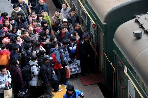Passengers board a train at a railway station in China's Anhui province on January 8, 2012.