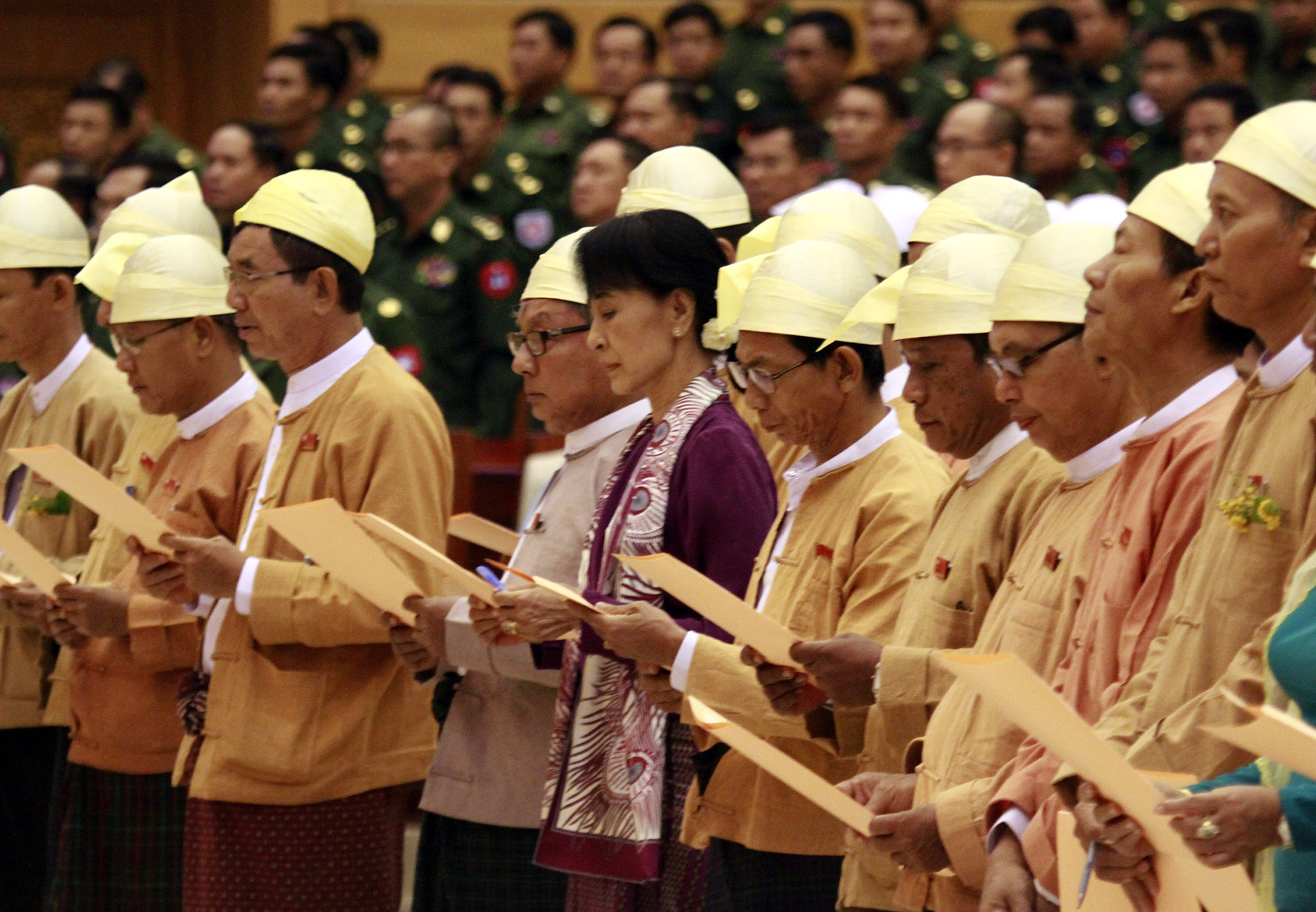 Myanmar pro-democracy icon Aung San Suu Kyi, center, and elected lawmakers of her National League for Democracy party swear during a regular session o...