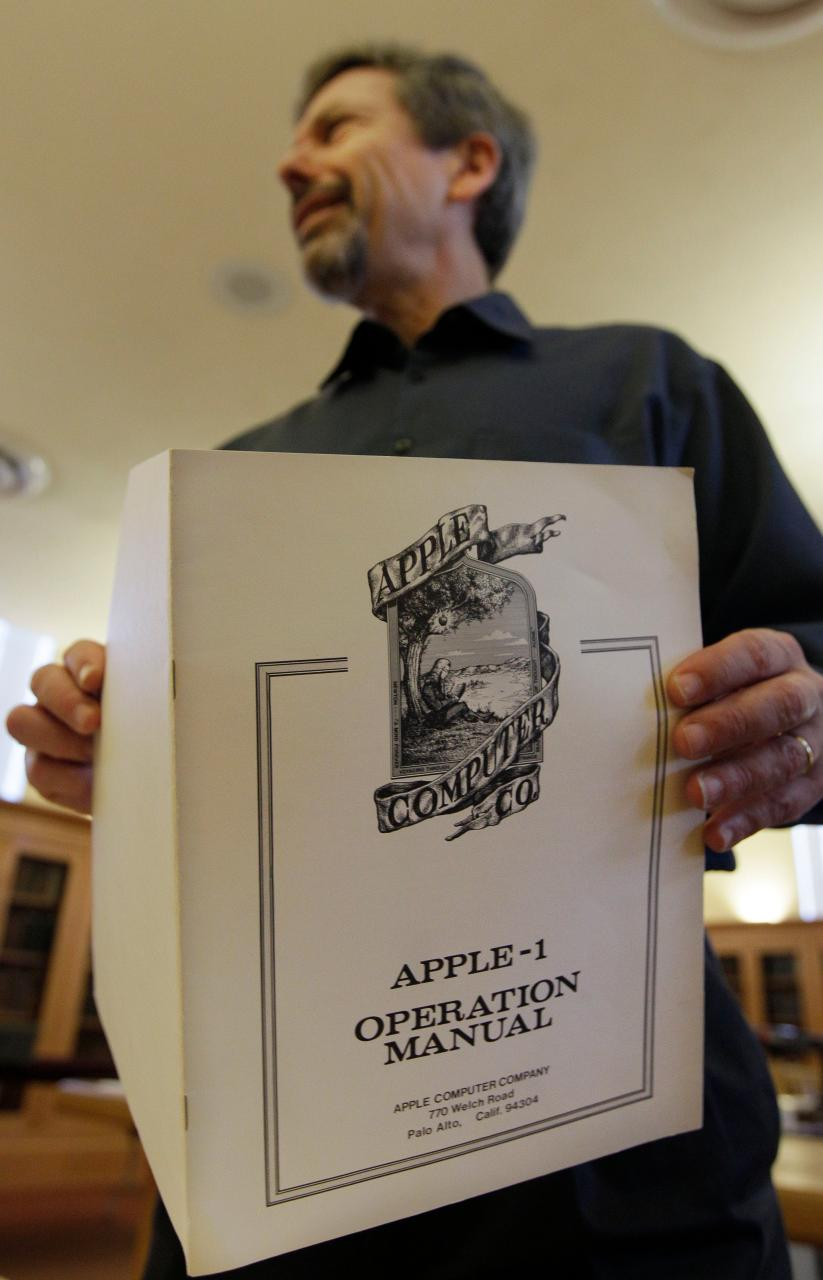 In this photo taken Oct. 25, 2011, curator Henry Lowood holds up an old Apple 1 operation manual at Stanford's Green Library in Stanford, Calif. Histo...