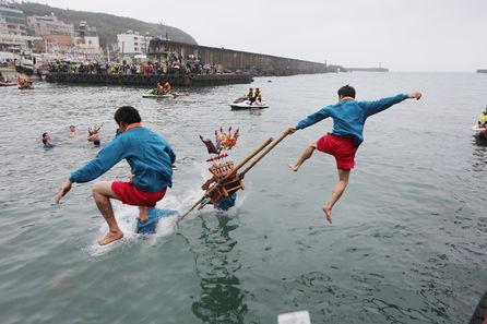 圖為去年野柳神明淨港文化祭,由勇士抬著神轎俯衝躍入野柳港中,象徵淨化港口、期望來年海上漁船作業平安。