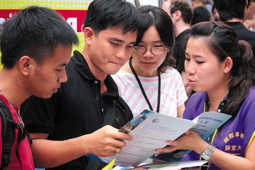 Two Filipino students collect information about schools during the fair.