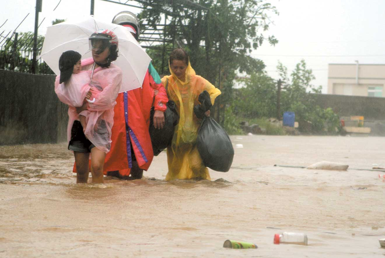Residents gathered their belongings to flee the rising waters in the Meishangmei area in Chiayi County yesterday, as torrential rain continued to lash...