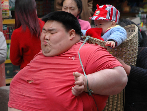 Twenty-six year-old Liang Yong, who weighed 220 kilograms at his heaviest, carries his child in a basket in China's Chongqing Municipality, in this fi...