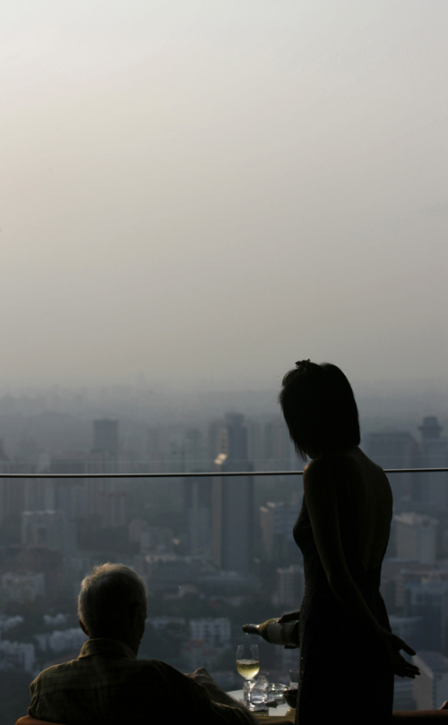 A waitress pours a drink as a man looks at the hazy skyline of Singapore yesterday.