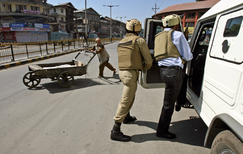 A Kashmiri man pushes a handcart as In dian security officers take up position a shootout in Srinagar, India yesterday.