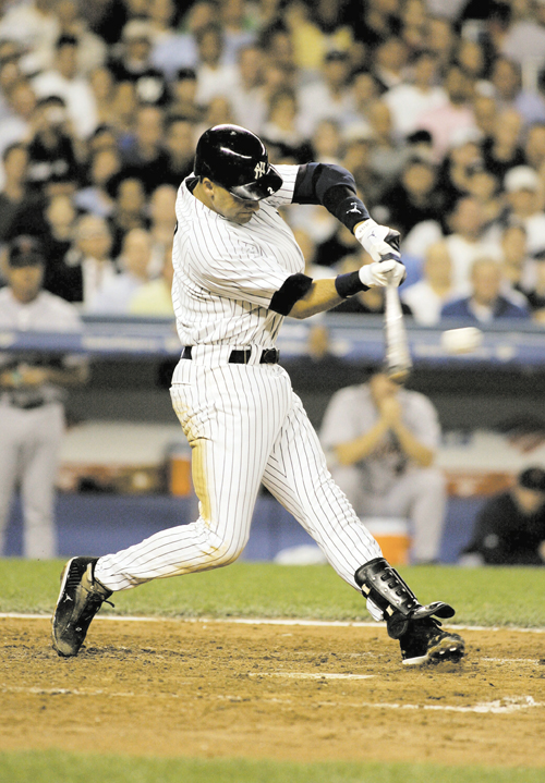 The New York Yankees' Derek Jeter connects for a hit in the third inning against the Detroit Tigers in Game 1 of the American League Division Series i...