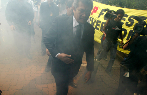 Indonesian Forestry Minister M.S. Kaban arrives for work amid smoke pumped out from a portable machine by Greenpeace activists during a demonstration ...