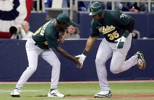 Oakland Athletics batter Frank Thomas, right, is congratulated by third base coach Ron Washington after hitting his second home run against the Minnes...