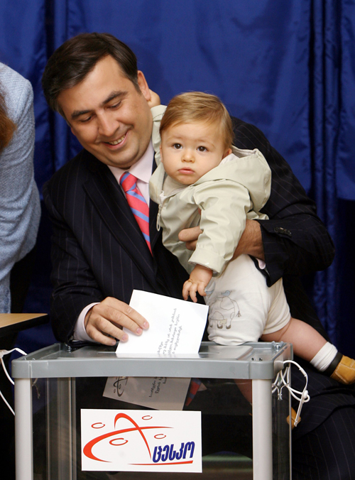 Georgia's President Mikhail Saakashvili casts his ballot while holding his son Nikoloz during local elections in Tbilisi yesterday.