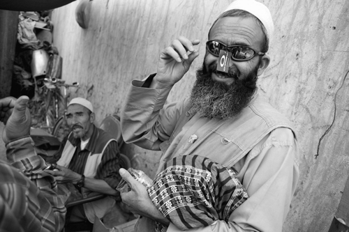 """Haji Nazekmir tries on a pair of Oakley Sunglasses he found at the """"Bush Bazaar"""" in Kabul, Afghanistan, last month. Piles of merchandise originating f..."""