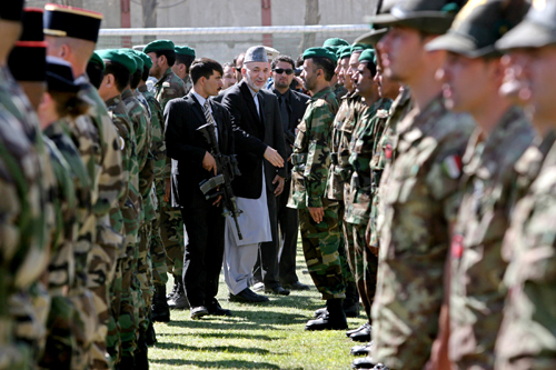 Afghan President Hamid Karzai, center, inspects Afghan and NATO officials at a ceremony in Kabul, Afghanistan yesterday.