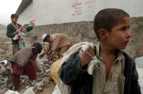 An Afghan boy holds a bag on his back as his friends collect recycle materials to burn for firewood, in the background, in Kabul, Afghanistan on Novem...