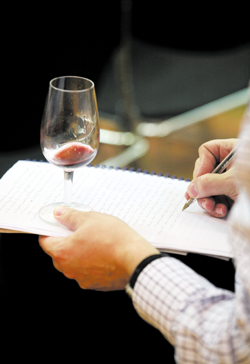 A buyer samples a glass of wine and makes notes during a wine auction at Christie's in London last month.