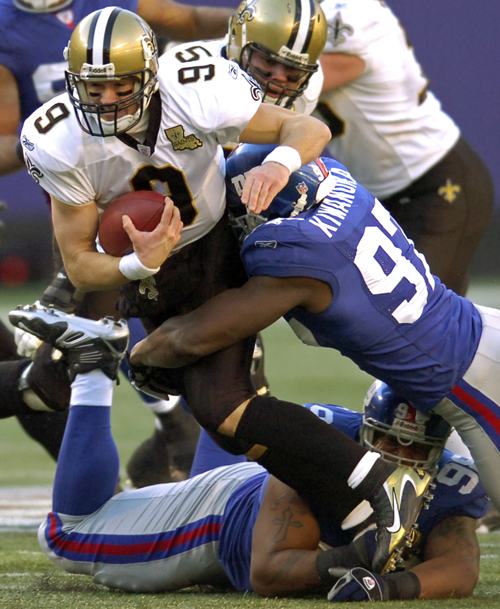 New Orleans Saints quarterback Drew Brees (9) scrambles for three yards before being tackled by the New York Giants' Mathias Kiwanuka, right, and Fred...