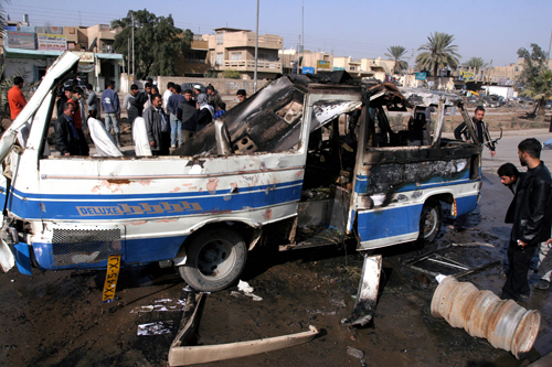 Iraqis look at a minibus destroyed in a suicide bomb attack in Baghdad, Iraq on Monday.