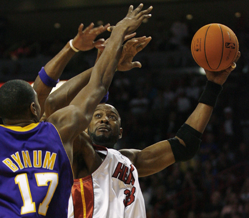 The Miami Heat's Alonzo Mourning, right, reaches over the defense of the Los Angeles Lakers' Andrew Byrnum during fourth quarter NBA basketball action...