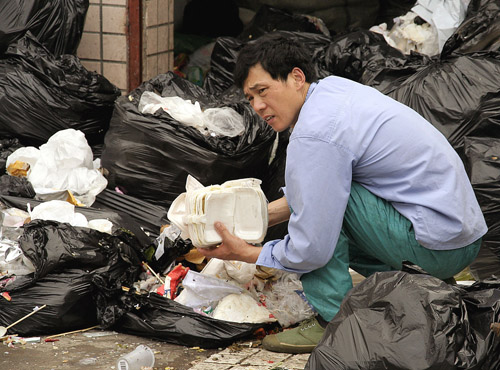 A garbage recycler searches for any plastic objects in Shanghai, China early this year. Poverty, water shortages, environmental crises: Asia's booming...