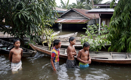 Indonesian youths play in a flooded village in Kampar of Riau province in Indonesia on Monday.