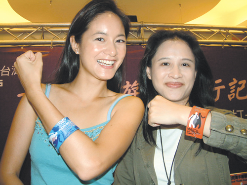 """Cheng Li-chiun, right, head of the National Youth Commission, and Janet Hsieh, host of Discovery Channel's """"Fun Taiwan,"""" promote the Youth Travel Card..."""
