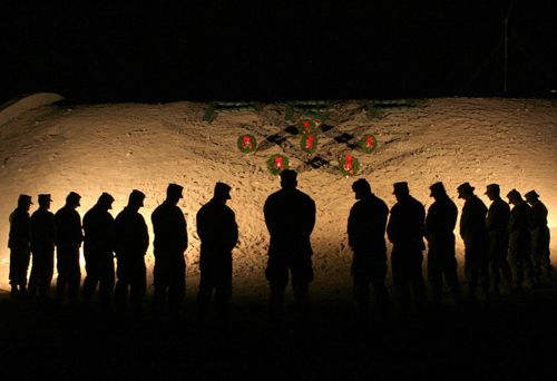U.S. Marines with the 1st Marine Logistics group bow their heads in silence in honor of fallen comrades during an evening vigil at Camp Al Taqaddum in...