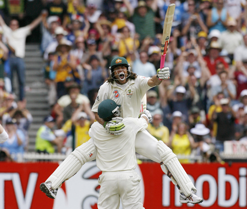 Australia's Andrew Symonds, right, hits a six to bring up his maiden test century as England's wicketkeeper Chris Read, left looks on during the secon...