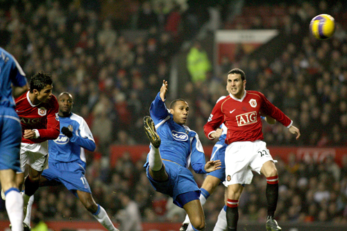 Manchester United's Cristiano Ronaldo, left, heads his side into the lead against Wigan Athletic during their English Premier League match in Manchest...