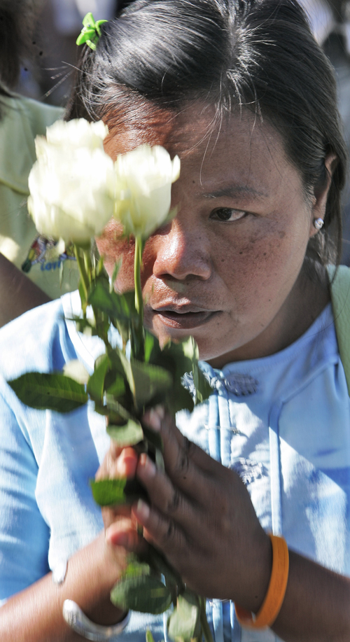 An unidentified Thai woman offers flowers and prayers during services in Khao Lak, Thailand on Tuesday.