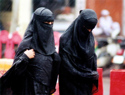 Veiled Indian Muslim women walk through a street during heavy rains in Bhopal, India in this August 25, 2002 file photo.